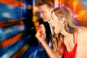Gambling couple in Casino or amusement arcade on slot machine wi